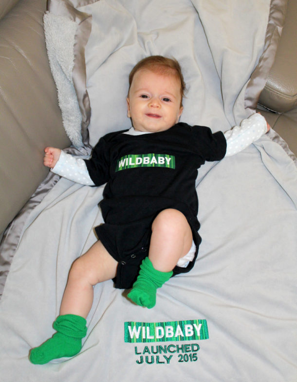 "Photo of a baby in a onesie with ""Wildbaby"" across the front on a blanket with ""Launched July 2015"" embroidered on it."