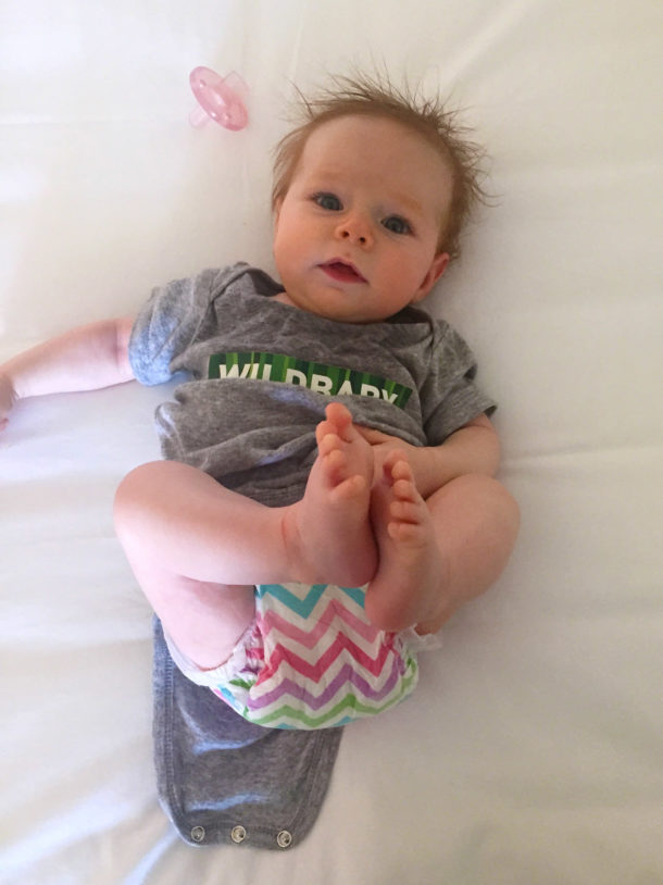 "Photo of a baby in a onesie with ""Wildbaby"" across the front."