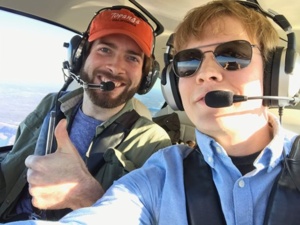 Photo of two people flying together in a small plane