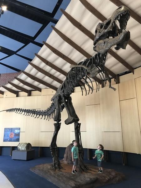 Photo of Jeremy's kids under a skeleton of a Tyrannasaurus Rex