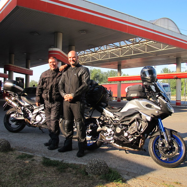 Photo of Milan and his friend standing by their motorcycles.